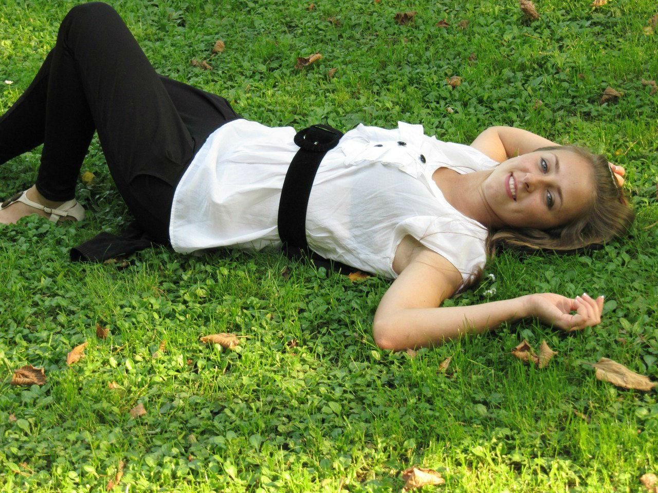 Светлорусая девчонка в белой тунике на траве