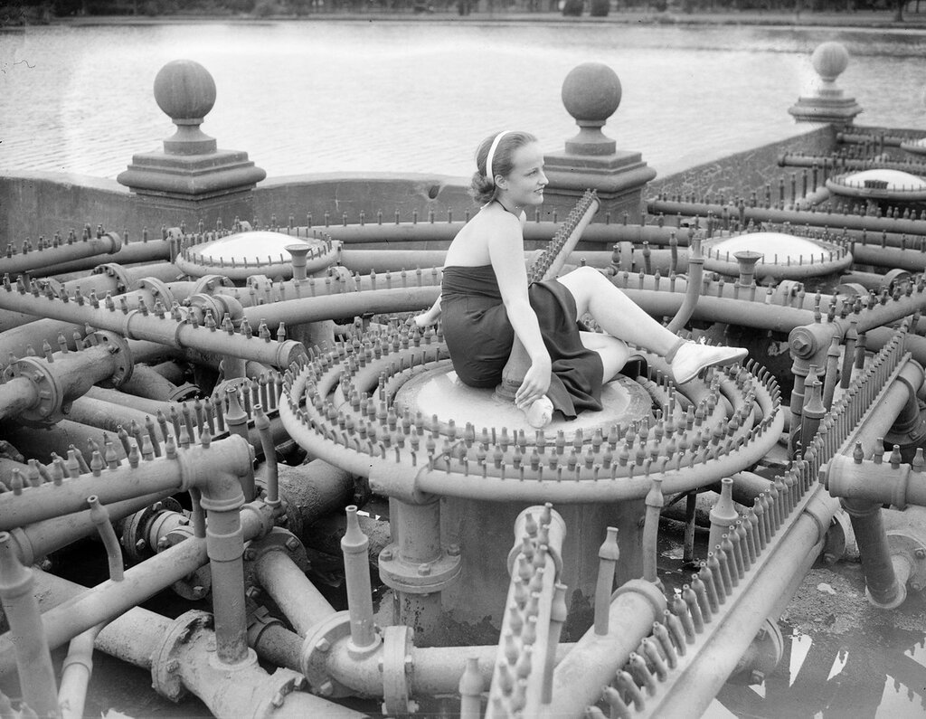 Woman sits in the center of the fountain that is in the middle of City Park Lake in Denver, Colorado, between 1930 and 1960
