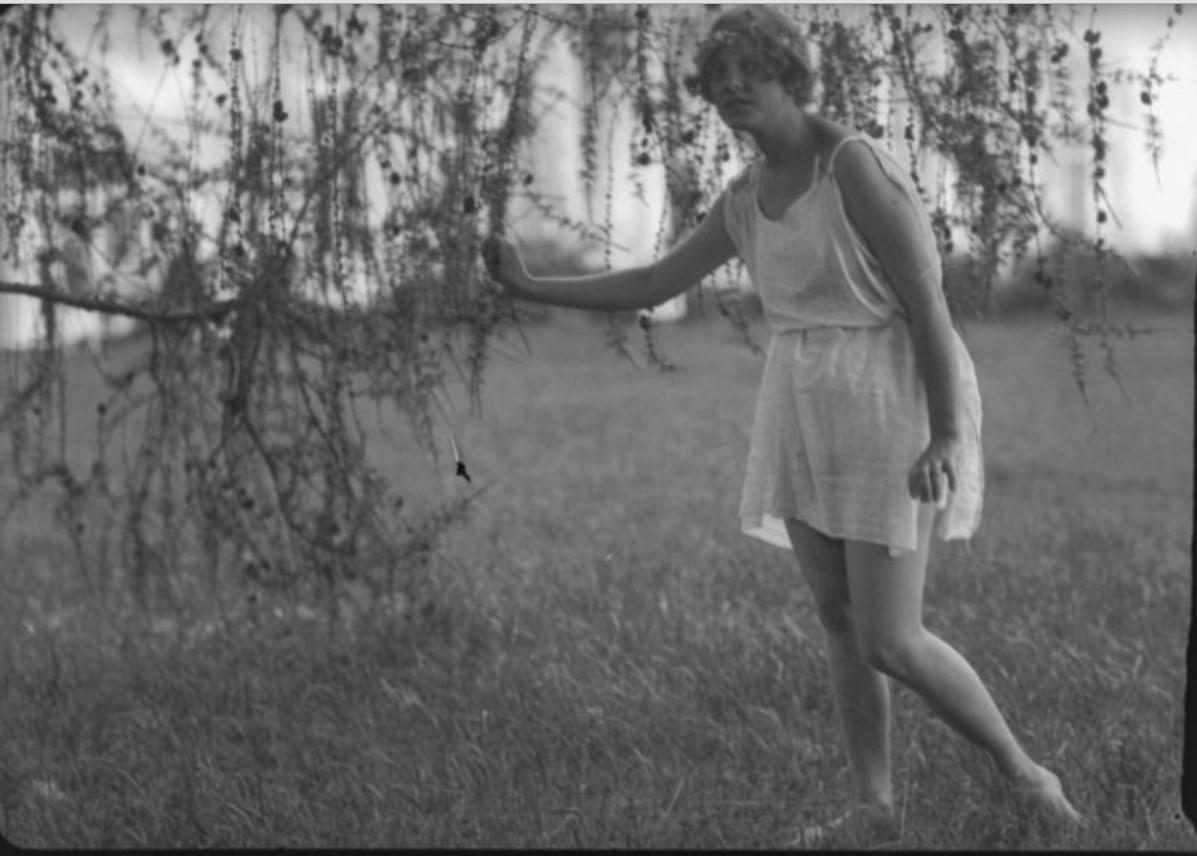 Девушка в тунике под ветвями лиственницы