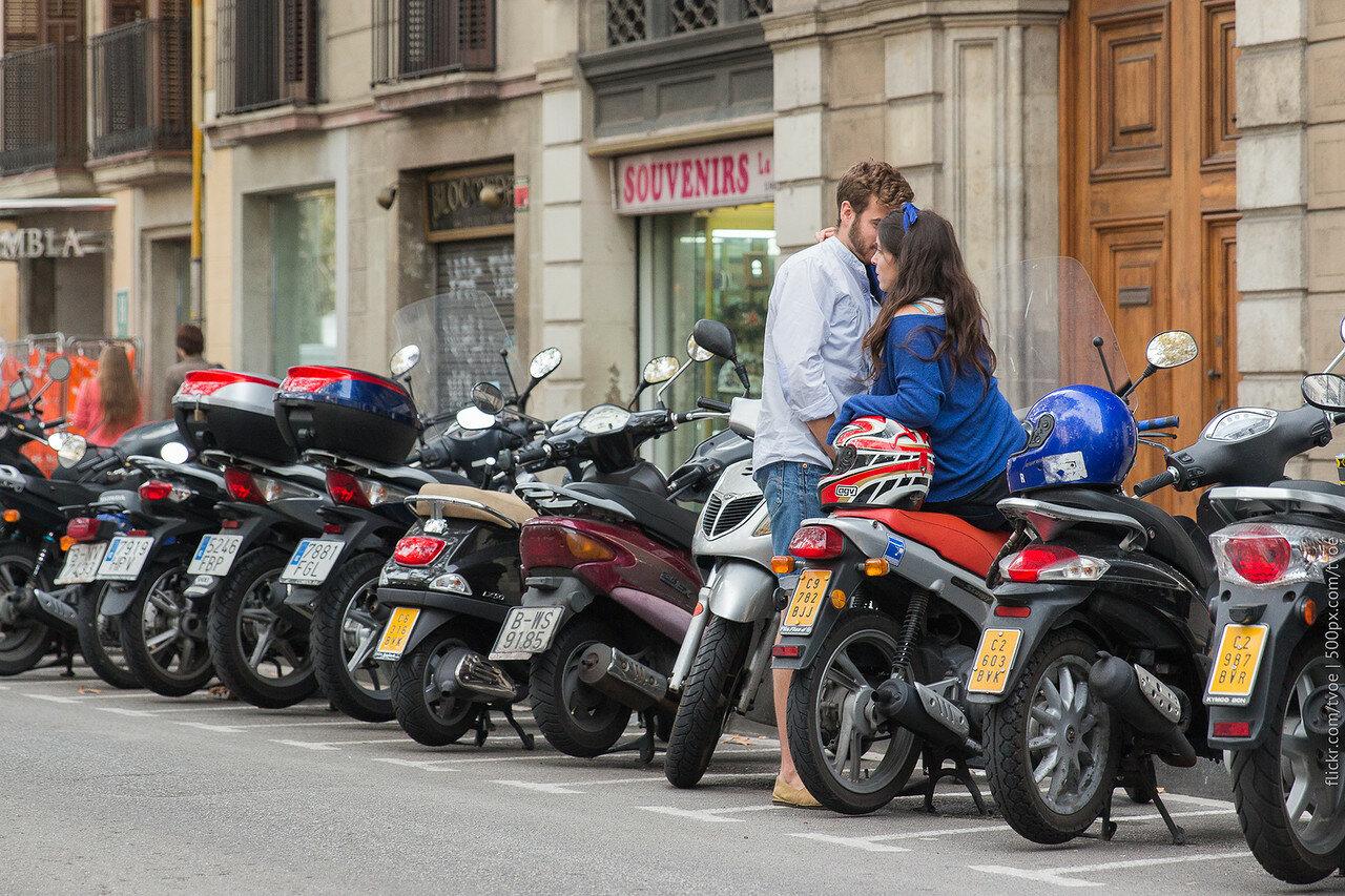 Мужчина и женщина обнимаются среди мопедов в Барселоне