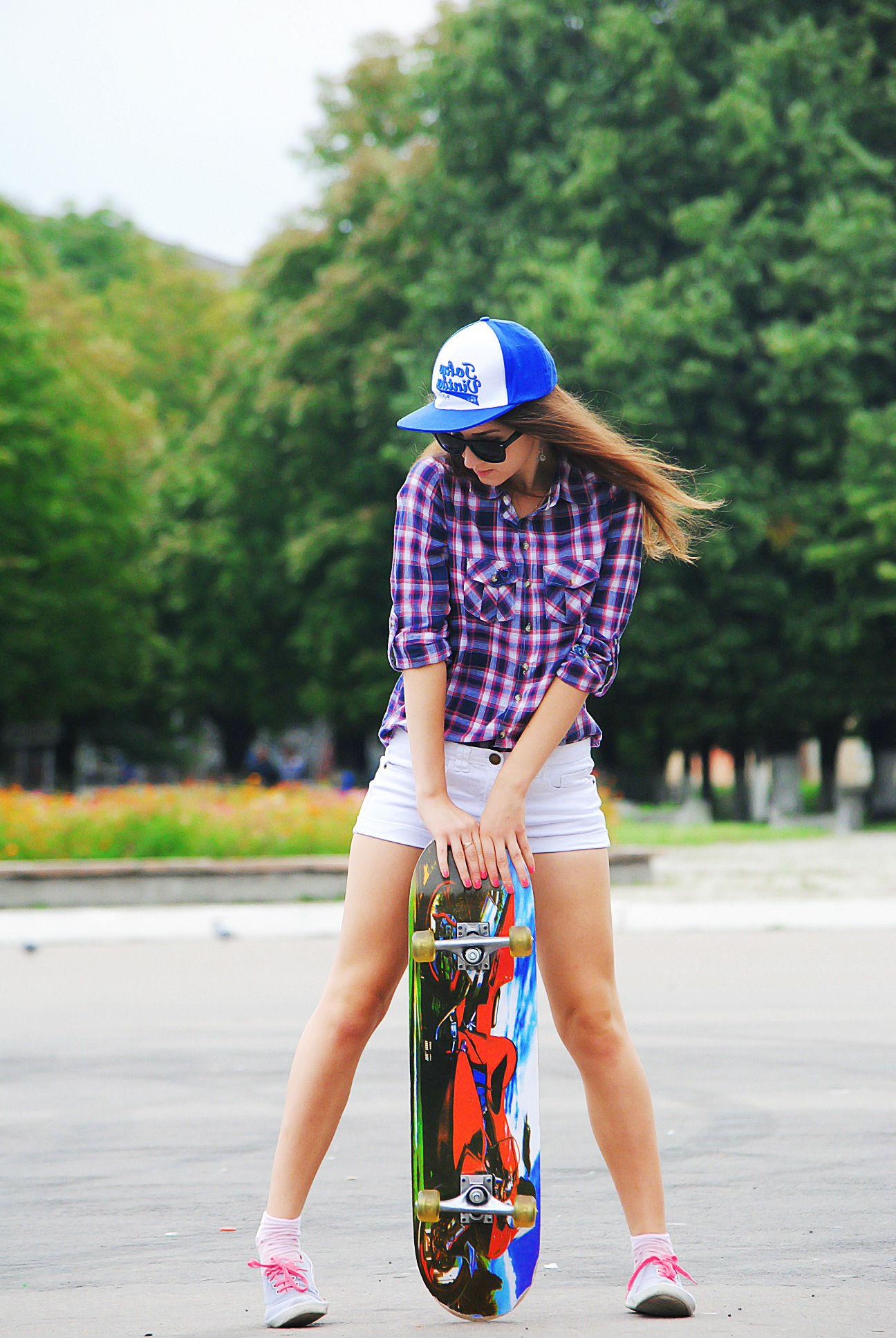 Спортивная школьница  в клетчатой рубашке на скейте