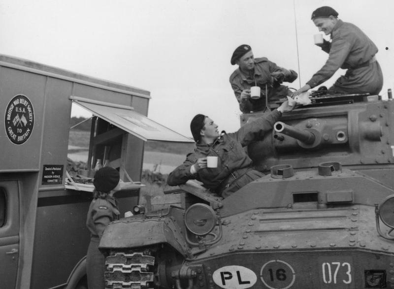 Crew of a Mark III Valentine tank of the 66th Battalion, 16th Tank Brigade talking to a female staff of a mobile canteen while enjoying a cup of tea during training exercises in Scotland, 1941.
