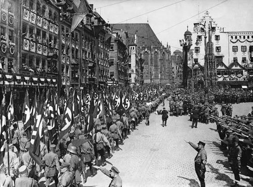 Nazi storm troopers marching through the streets of Nürnberg, Ger., after a Nazi Party rally.[Credits : Bettmann/Corbis]