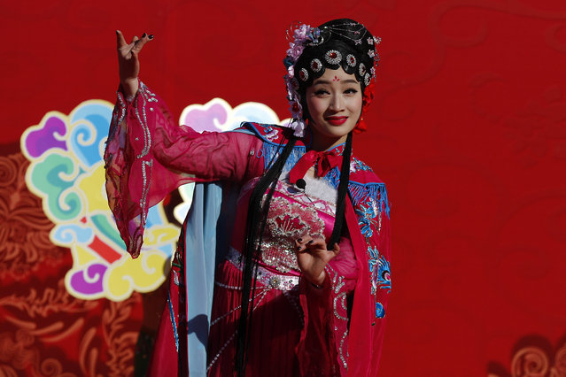 A Chinese performer dressed in traditional costume performs a cultural dance during a temple fair fo