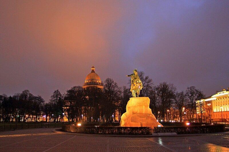 Медный всадник и купол Исакиевского собора на фоне тревожно-красного вечернего неба в Санкт-Петербурге.