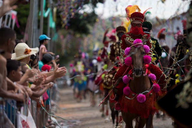 People applaud as revellers participate in the traditional Carnival on horseback, a tradition dating