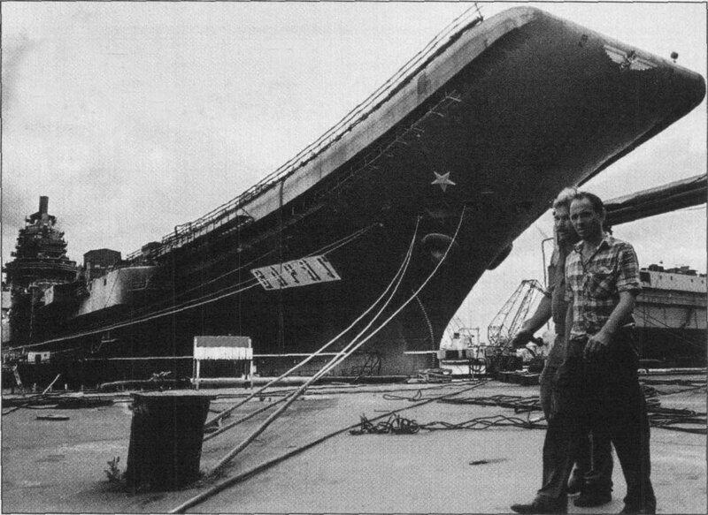 """Рабочие Черноморского судостроительного завода в Николаеве проходят мимо недостроенного авианесущего крейсера """"Варяг"""" на верфи завода в мае 1997 года"""