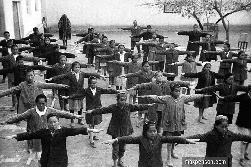 32. Урок физкультуры в школьном дворе. На заднем плане - женщина в