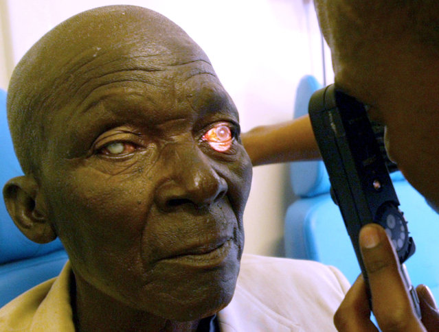 A student doctor conducts an eye test at Kimberley train station in South Africa June 29, 2004. (Pho