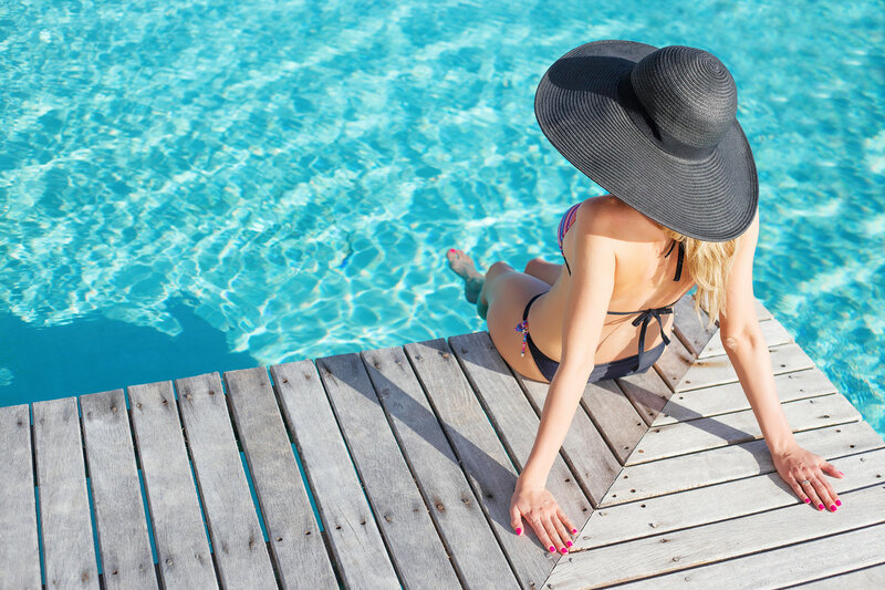 Woman sitting on the deck by the pool