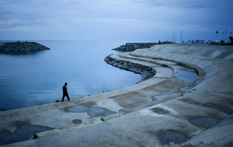 Мужчина прогуливается по берегу. Трабзон, Турция.
