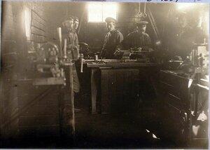 Солдаты в мастерской за работой на токарном, строительном и болторезном станках.