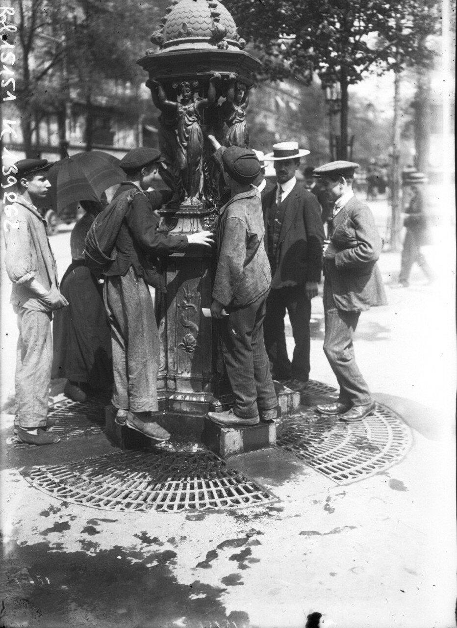 1911. Люди пьют из фонтанчика