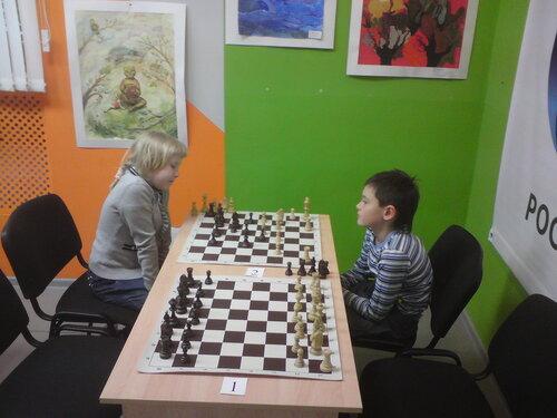 девочка играет с мальчиком в шахматы