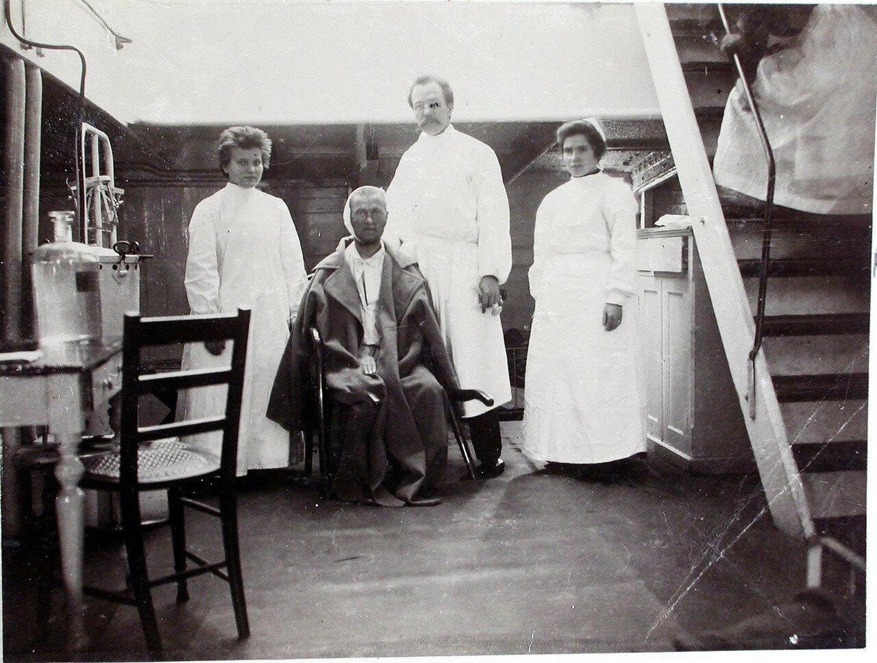 26. Младший врач В. П. Ивакин и сестры милосердия около больного в палате № 3. 1901