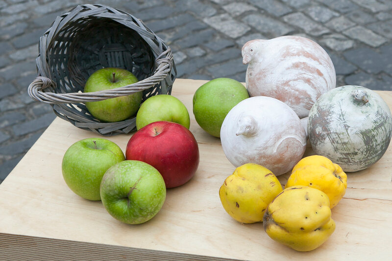 Autumn composition decorating the counter. Apples, quinces and lemons, together with eucalyptus and daisies on the table