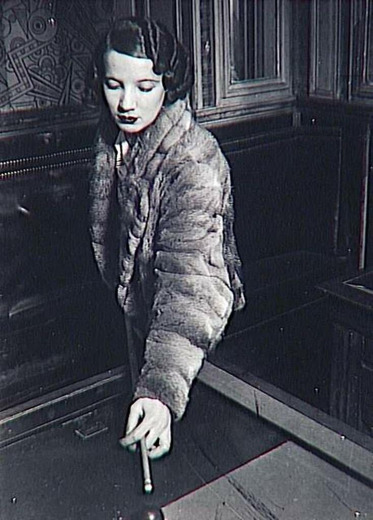 1932. Проститутка в мехах играет в русский бильярд на бульваре дё Рошешуар, Монмартр, Париж