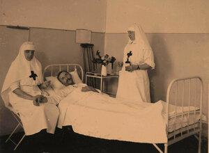 Сестры милосердия у постели раненого офицера в 4-й палате;слева-старшая сестра лазарета Л.В.Никитина.