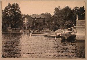 Вид жилого дома на берегу  озера в дачной местности Пикруки; справа - лодочный причал.