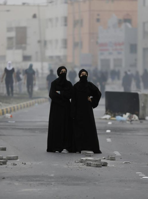 Bahraini anti-government protesters standing in tear gas and smoke from burning debris look toward police positions during clashes Saturday, Feb. 14, 2015, in the Manama suburb of Daih, Bahrain. Protesters took to the streets in predominantly Shiite areas of Bahrain and set tires alight along a major highway Saturday to mark the fourth anniversary of widespread protests calling for reform in the island nation. (AP Photo/Hasan Jamali)