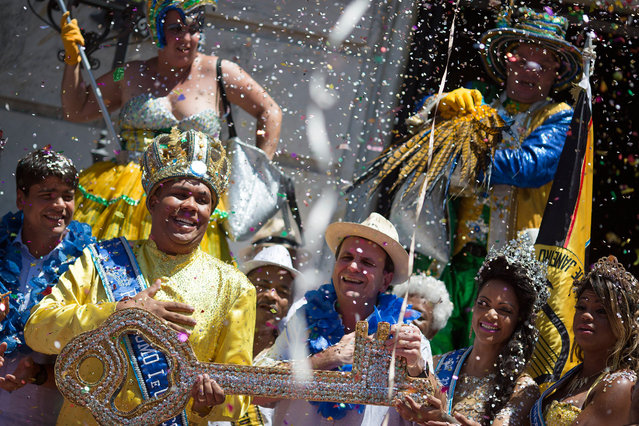 The 2016 Carnival King Momo, Wilson Dias da Costa Neto, left, holds the key of the city with Rio de