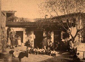 Группа местных жителей во дворе дома.