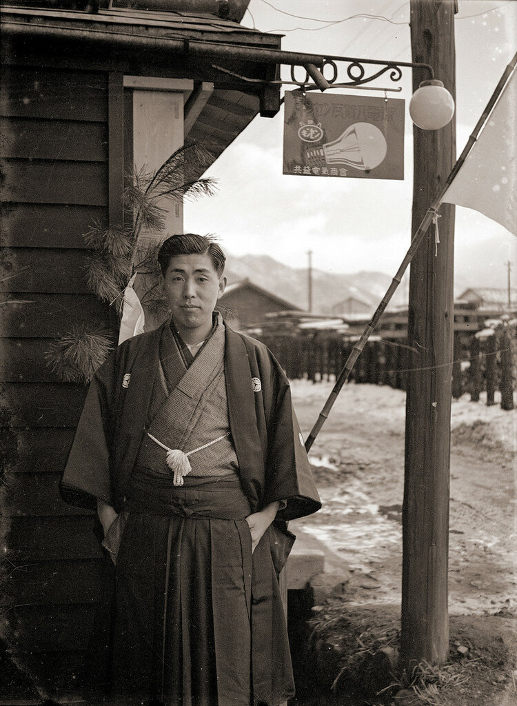 Japanese Man in Hakama, 1930s Japan. The sign with the light bulb advertises a supplier of electrical goods called Kyokeki Denki Shokai.