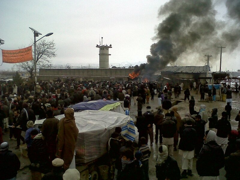 People gather near a fire at Bagram airb