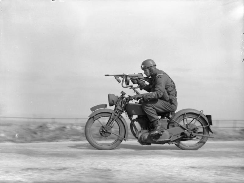 A guardsman of 1st Battalion, Grenadier Guards, 3rd Division, riding a motorcycle with a 'Tommy gun' fitted to a special mounting, Swanage, 9 April 1941.jpg