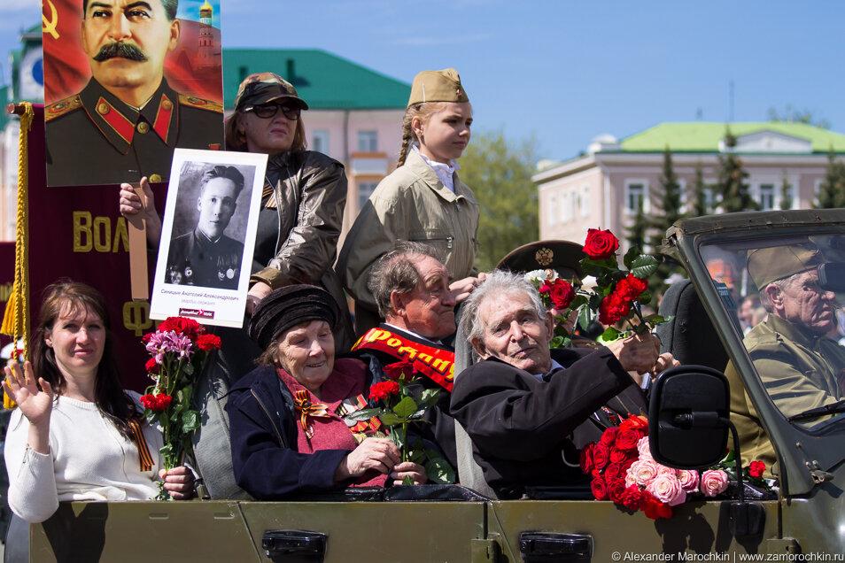 Ветераны ВОВ с портретом Сталина на параде