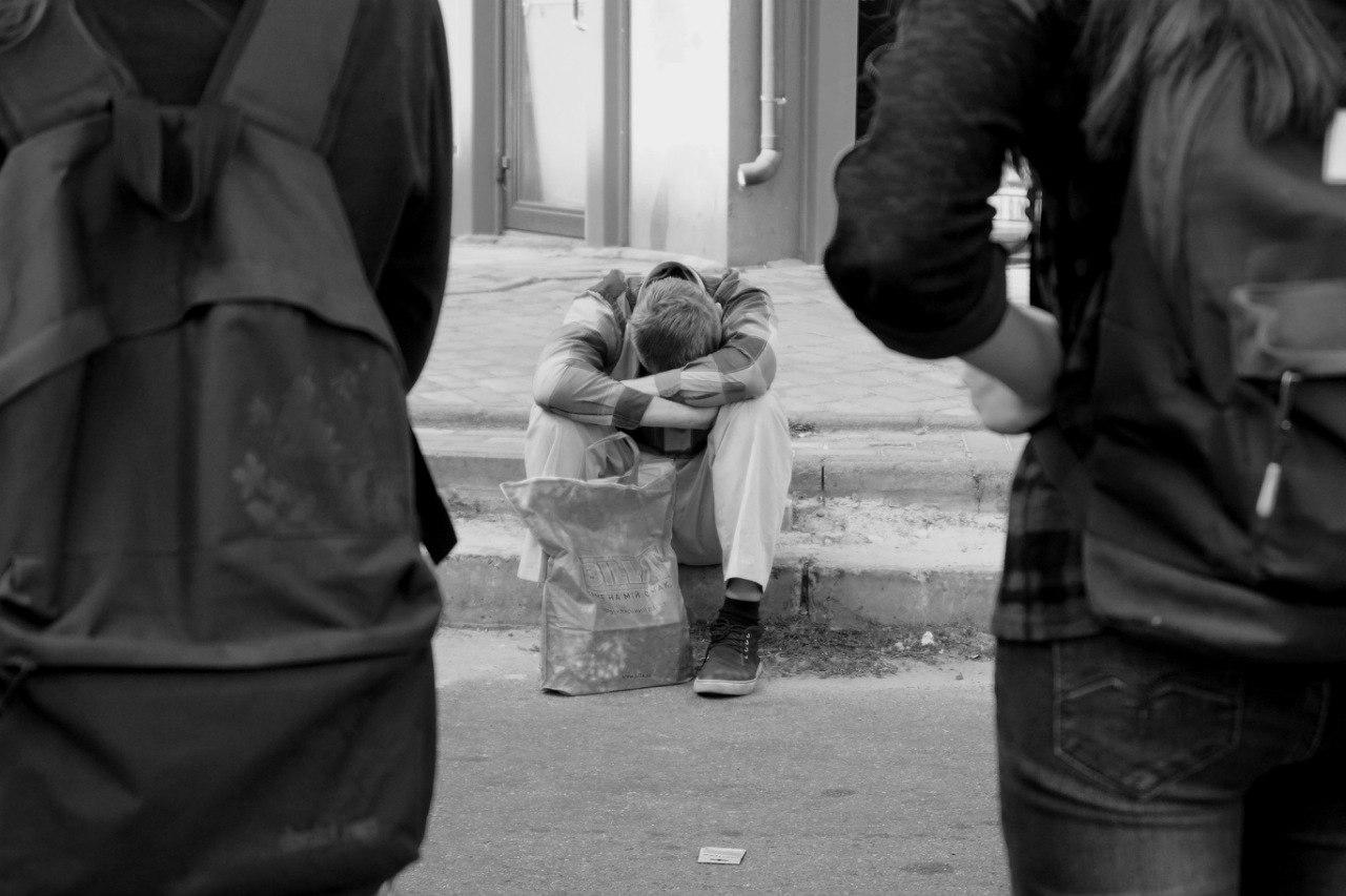 человек устал спит на тротуаре