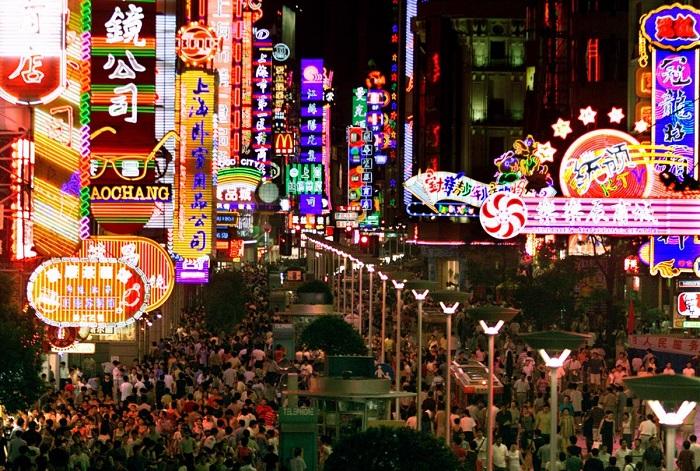 Покупатели толпятся под красочными неоновыми огнями вдоль оживленной Нанкинской улицы Шанхая. 21. Пе
