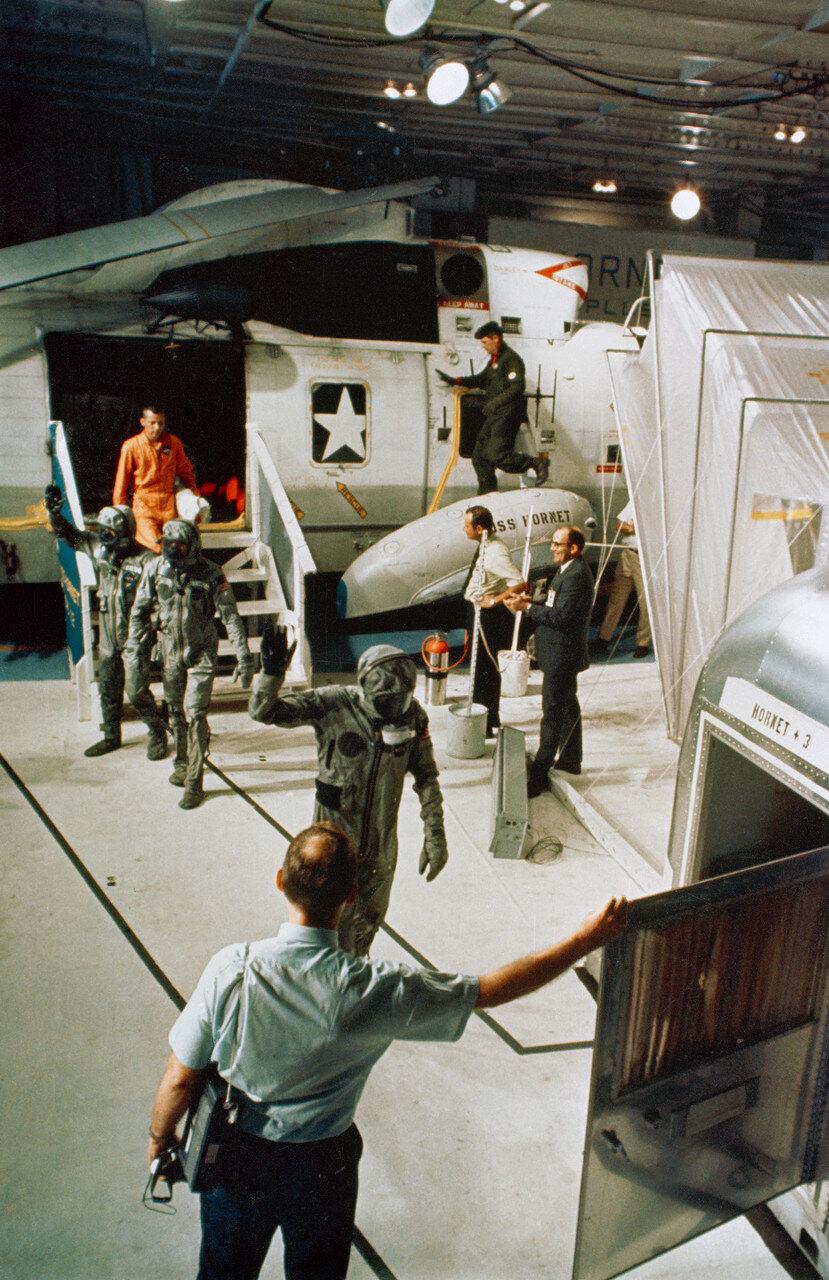 Экипаж подняли на борт вертолёта и доставили на авианосец через 63 минуты после приводнения. На снимке: Экипаж «Аполлона-11» на борту авианосца «Хорнет» переходит из вертолёта в карантинный фургон. Впереди — Коллинз, за ним — Армстронг и Олдрин