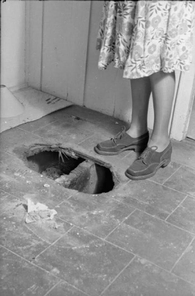 11. Оливия стоит возле дыры в полу, сделанной во время пожара от бомбы, прежде, чем огонь удалось взять под контроль. Это часть дома не имеют асбестовых плит на полу
