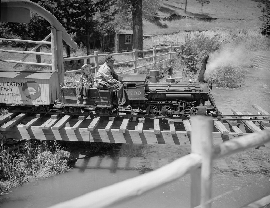 Engineer Harry Altig drives Train No. 1700, a small scaled coal burning steam engine, across a bridge in Tiny Town, Turkey Creek Canyon, Jefferson County, Colorado. July 8, 1947.