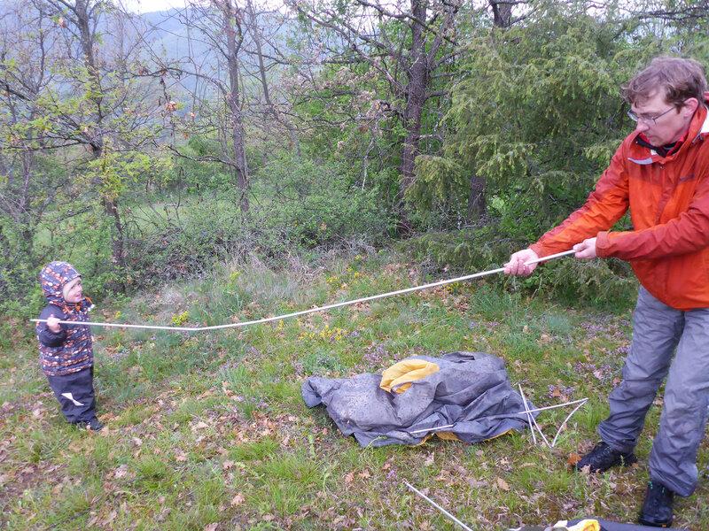 ребенок помогает папе устанавливать палатку в походе