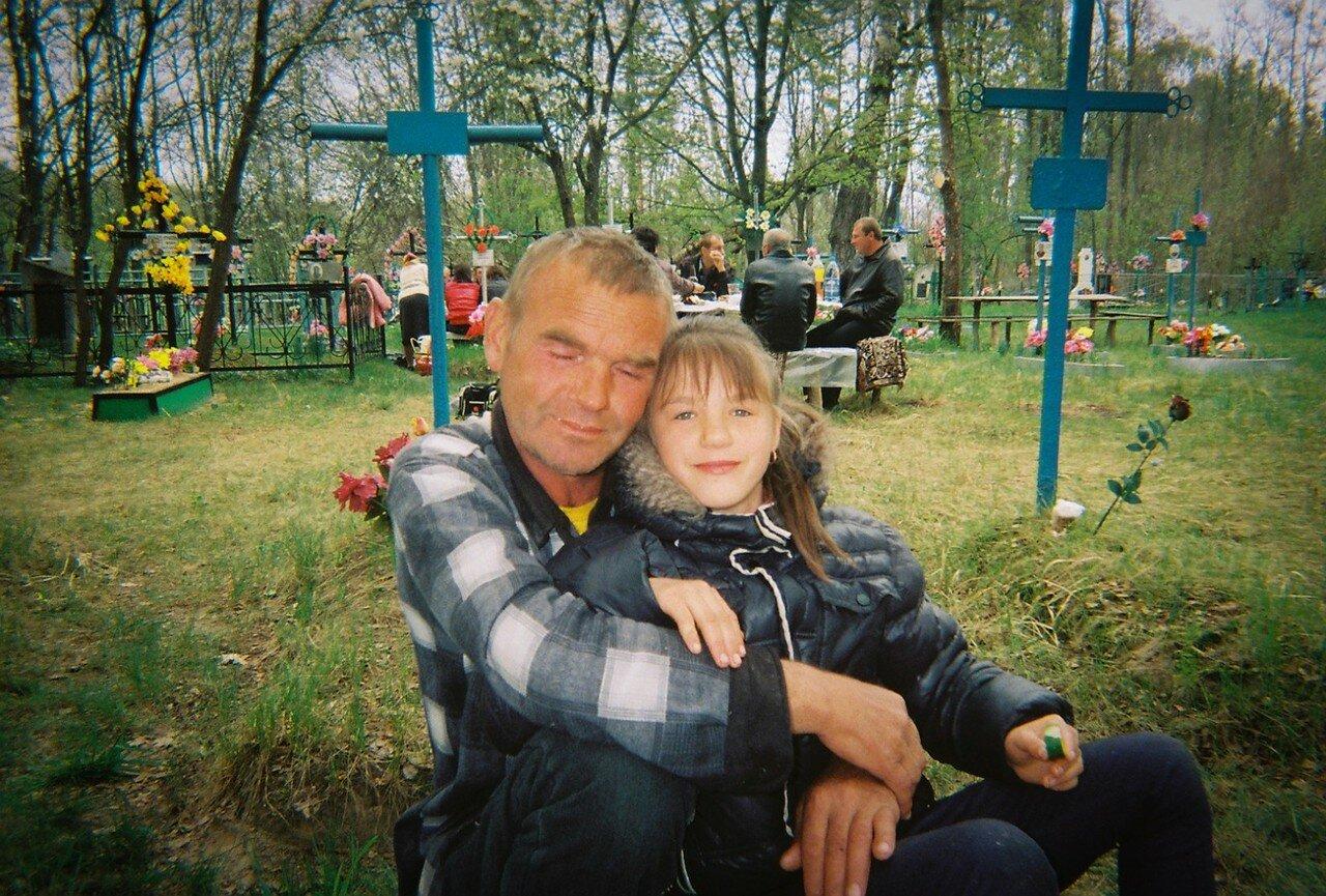 Отец и дочь на местном кладбище в зоне отчуждения во время празднования Пасхи