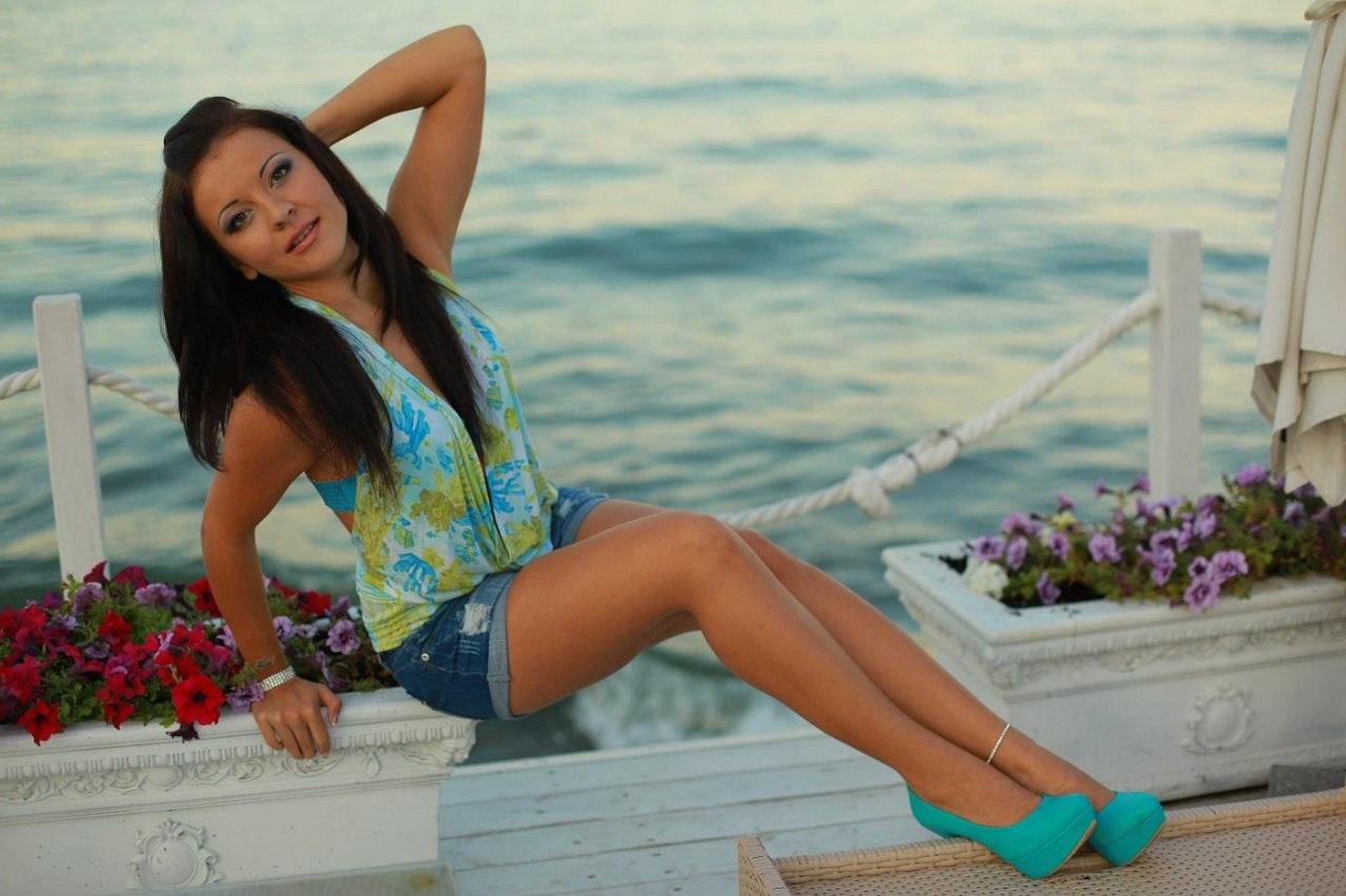 Яркая девчока  в мини-шортах на фоне моря