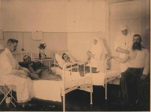 Врач и сестры милосердия проводят сеанс массажа раненым офицерам.