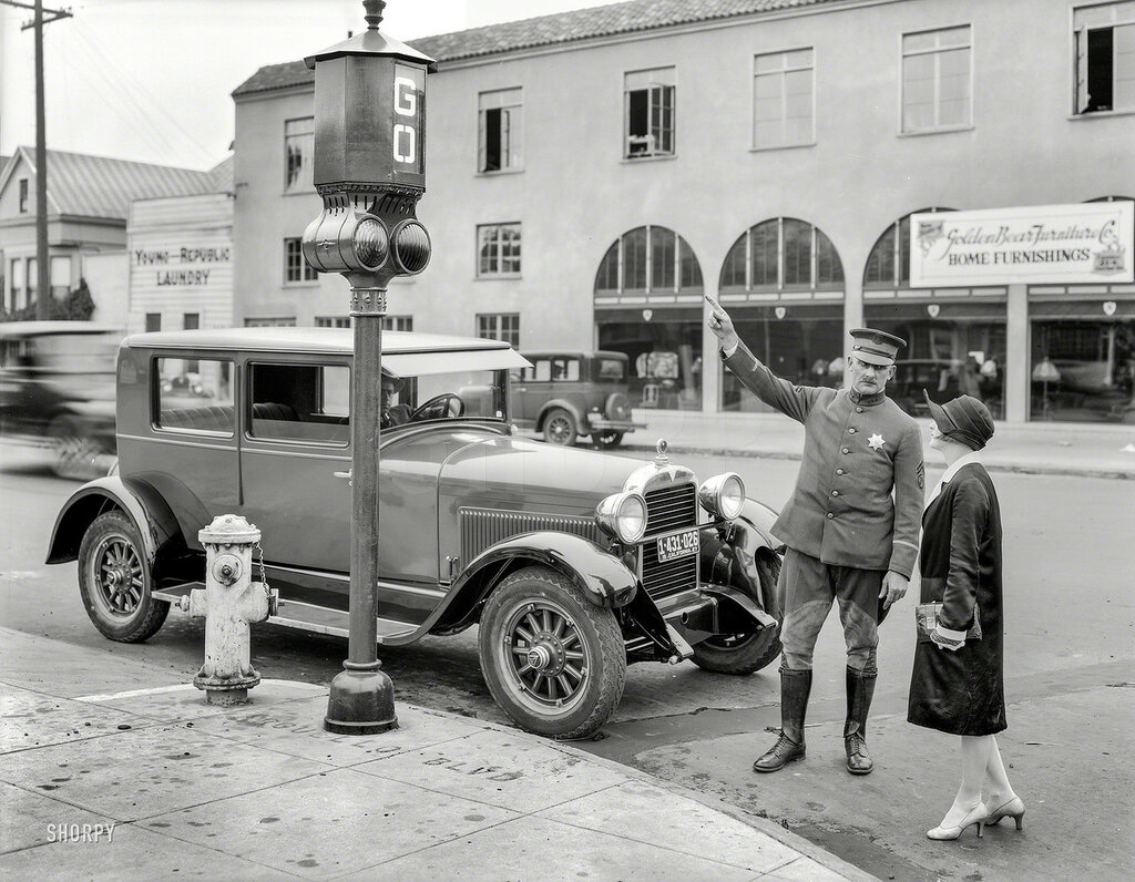 San Francisco, 1927. Traffic signals -- police officer stops pedestrian crossing against the light on Arguello Boulevard