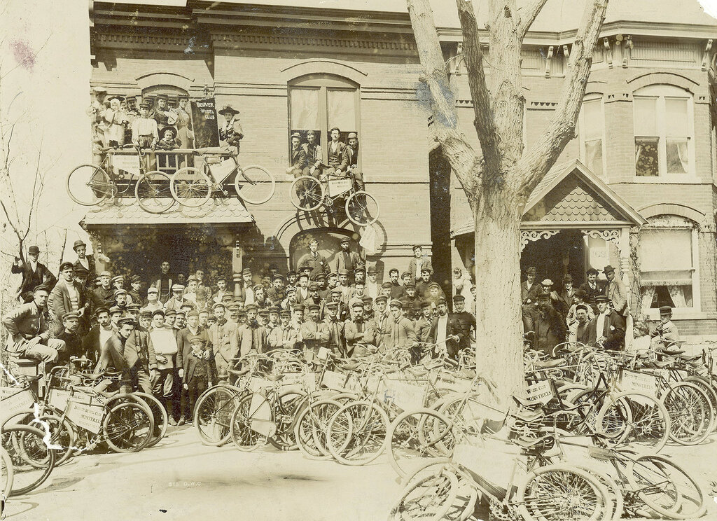"Men and bicycles crowd the front of a house in Denver, Colorado; signs read ""Denver Wheel Club"". Women on a balcony have a sign ""Denver Wheel Club Minstrels"". between 1890 and 1910"