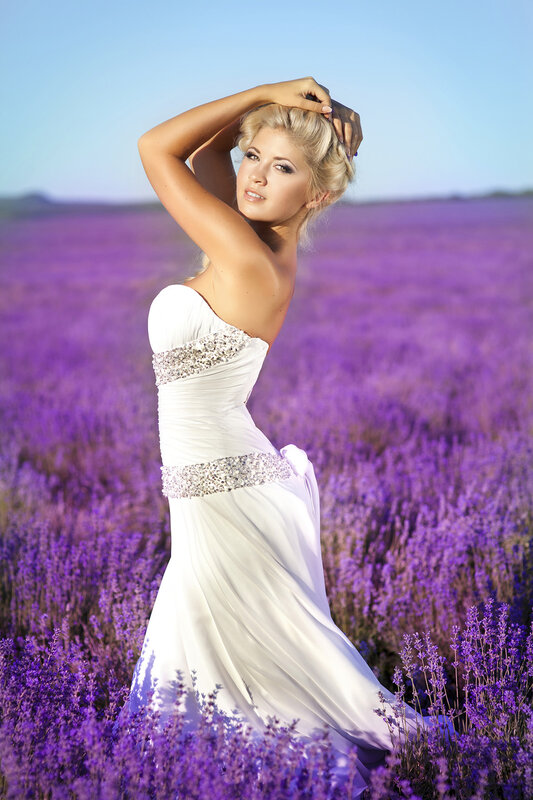 Beautiful bride in lavender field at wedding dress