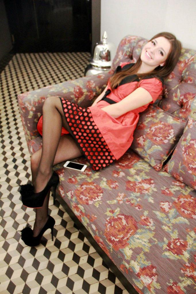 Веселая шатенка на диване в колготках