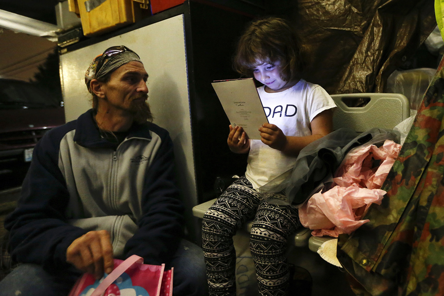 Emma Savage, 6, opens a birthday card given to her by her dad Robert Rowe, 42, a day laborer who had
