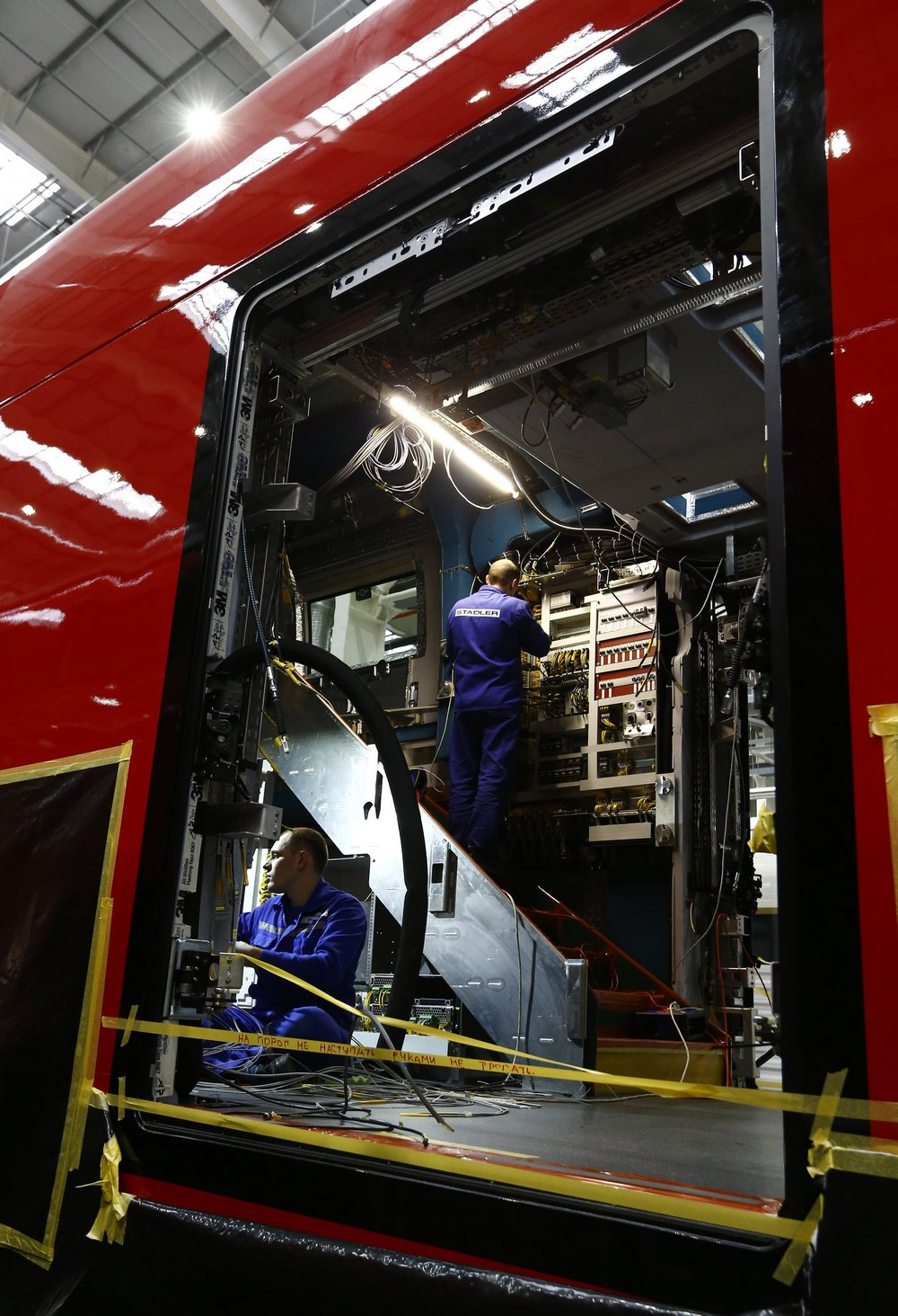 Employees work on an electric train assembly line at the Stadler Minsk plant in Fanipol