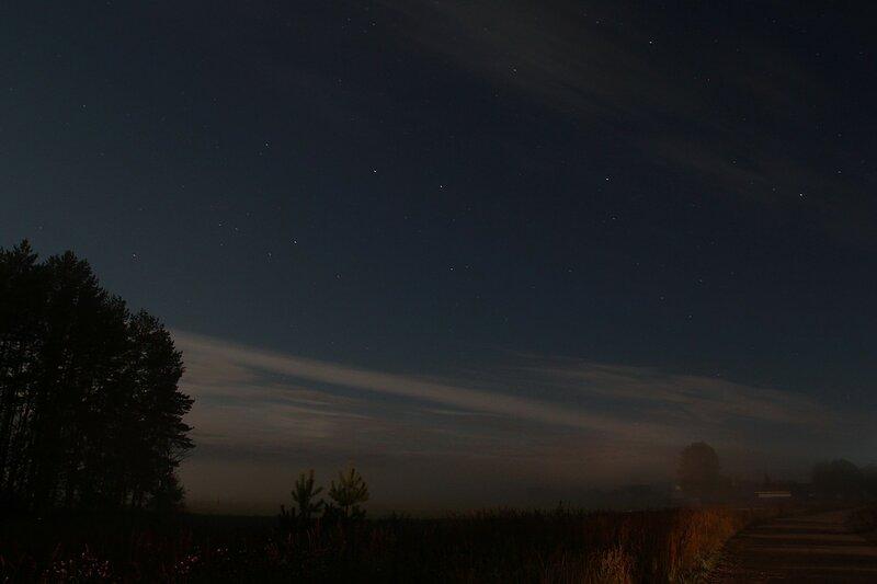 Звездное небо с облаками, туман на полях и лунные тени от деревьев на дороге