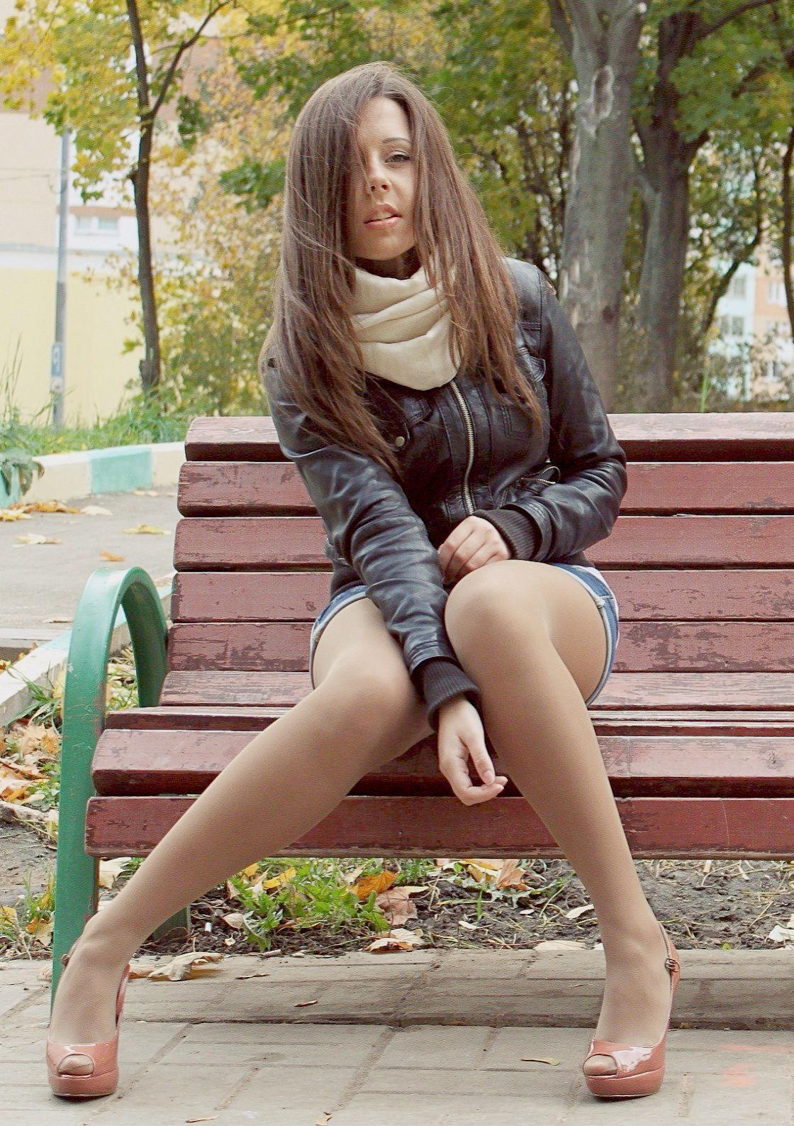 Заводная шатенка на скамейке с красивыми ножками