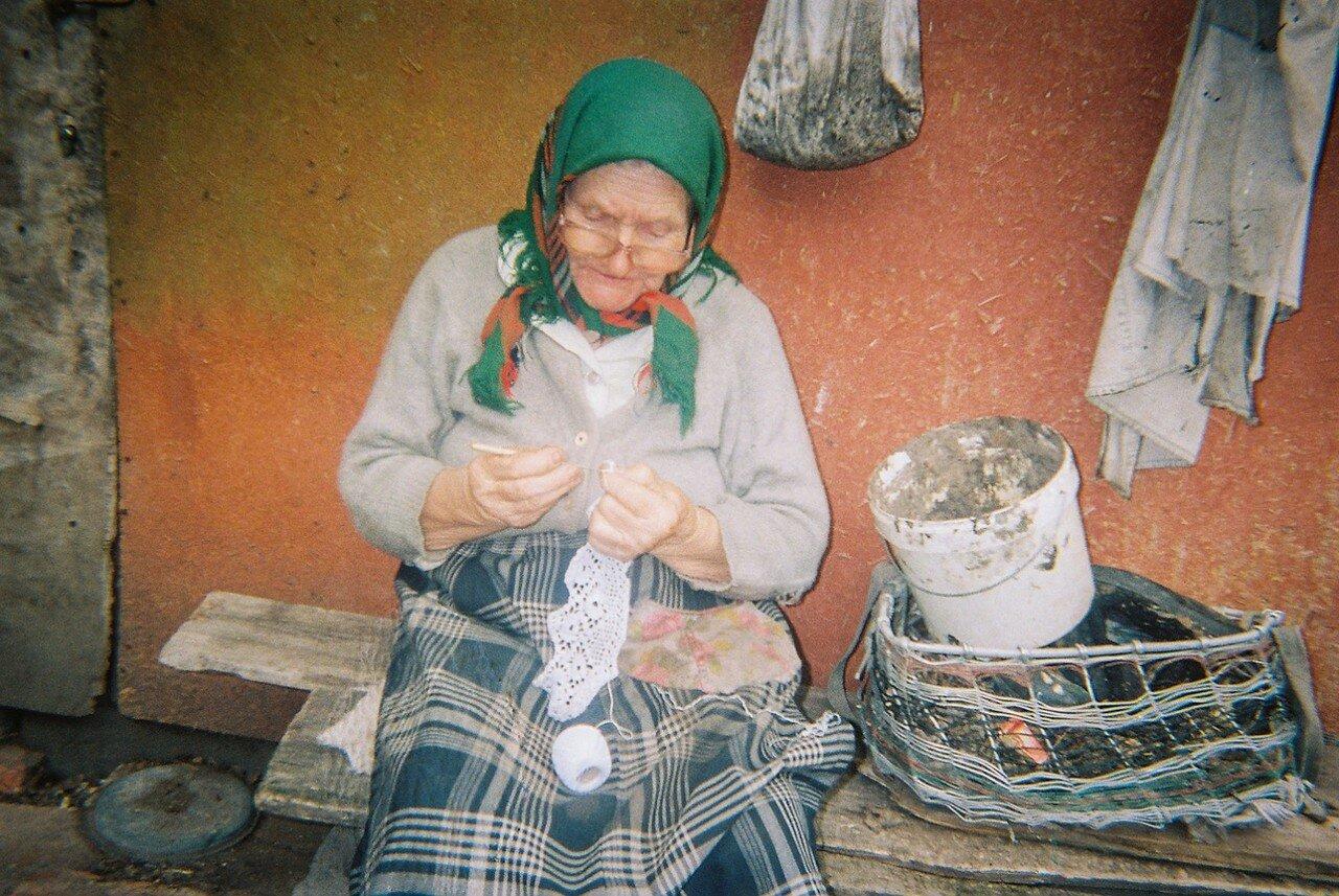 Пожилая женщина вышивает на скамейке возле дома
