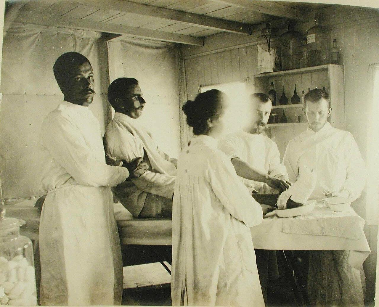 36. Медицинский персонал за перевязкой раненого в перевязочной Елизветградской баржи-лаза