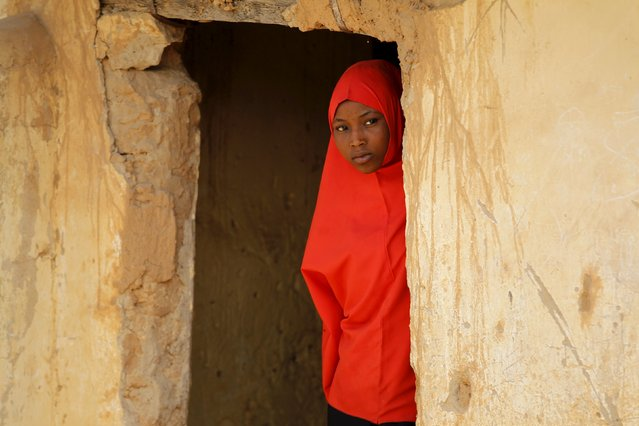 A girl peers out of a doorway at a local Islamic school in Zaria, Kaduna state, Nigeria, February 2,